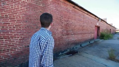 Teenager Walks in Slow Motion Near Old Brick Building Stock Footage