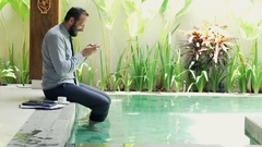 Young businessman playing game on smartphone sitting by pool Stock Footage