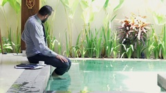 Young businessman smoking cigarette sitting by pool in outdoor villa Stock Footage