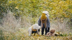Little daughter with her mother plays with yellow leaves in autumn park Stock Footage