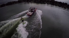 Aerial shot of a man wakeboard wake surfing behind a boat on a lake, slow motion Stock Footage
