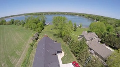 Aerial shot of a lake house and a boat dock, slow motion. Stock Footage