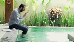 Successful businessman with tablet computer sitting by pool in outdoor villa Stock Footage