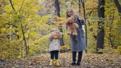 Little daughter with her mother and Teddy Bear walking in autumn park - waving Stock Footage