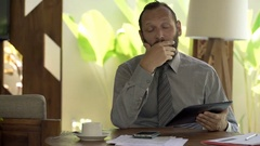 Unhappy businessman with tablet talking bad news to camera at home Stock Footage