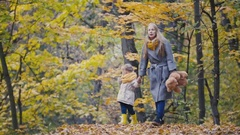 Little daughter with her mother and Teddy Bear walking in autumn park Stock Footage