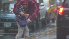 Pedestrian struggles to cross street in typhoon wind and rain Stock Footage