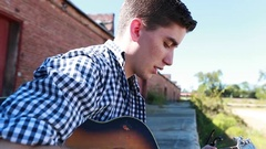 Teenager Plays Guitar in Slow Motion Detail with Old Brick Buildings Stock Footage