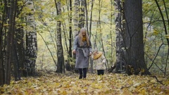 Little daughter with her mother walk in the autumn woods and kicked the yellow Stock Footage