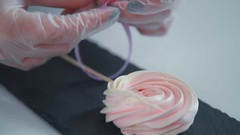 Women's hands are decorated meringue with stick and to tie the ribbon Stock Footage