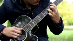 A young man playing acoustic guitar in the park Stock Footage