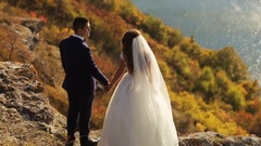 Young bride with long brown hair and her husband staying on the hill of the Stock Footage