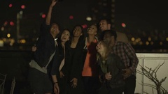 4K Happy mixed ethnicity friends pose for a selfie on city rooftop at night Stock Footage