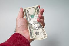 Male hand holds 20 dollars and pills Stock Photos