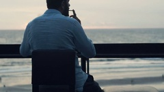 Man smoking cigarette and drinking beverage on terrace in bar during sunset Stock Footage