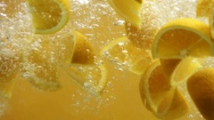 Sliced oranges falling into water Stock Footage