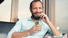 Happy man raising toast to camera and drinking cocktail in cafe Stock Footage