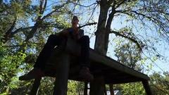 Teenager Plays Guitar on Tree Platform Handheld Silhouette in Slow Motion Stock Footage