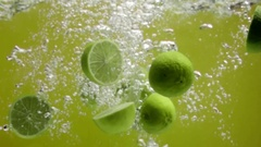 Sliced limes falling into water Stock Footage