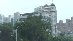 Establishing shot of apartment building and trees in typhoon Stock Footage