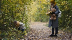 Little daughter with her mommy walking in autumn park - plays and hides behind Stock Footage