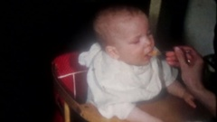The baby is eating as fast as mom can feed him, 3759 vintage film home movie Stock Footage