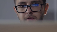 Man in black rim glasses using his computer in office. Businessman with Screen Stock Footage