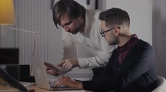 Two young businessmen discussing data in touchpad at meeting. Group of handsome Stock Footage