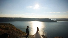 Young handsome groom in suit and the bride in a white elegant dress standing on Stock Footage