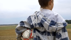 Boy dreams of becoming a football player, boy walking in the field with the ball Stock Footage