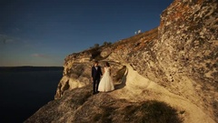 Stylish young groom holding hand and kissing his gorgeous bride at mountains Stock Footage