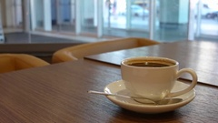 Cup of americano on a table and opening and closing doors of department store on Stock Footage