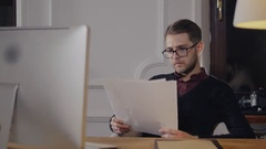 Cheerful businessman with glasses in the office receiving news, he is holding a Stock Footage