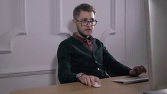 Multitasking. Handsome young man wearing glasses and working withlaptop while Stock Footage