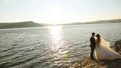 Happy kissing wedding couple holding on a stone of the mountain Stock Footage