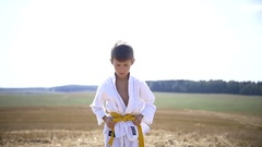 Boy in a kimono show kicks of karate in nature at the top Stock Footage