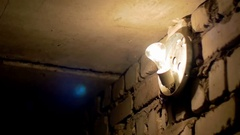 Filament Bulb Lights Off on a Stone Wall Stock Footage