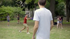 Guys playing frisbee - throwing and catching Washington Square Park summer NYC Stock Footage