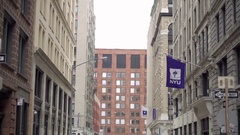 NYU building with flag, tilting down little street people crossing cobblestone Stock Footage