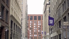 NYU flag on building in Greenwich Village tilting down to cobblestone street NYC Stock Footage