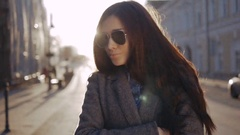 Woman in coat and sunglasses in autumn park. Student girl walking in glasses and Stock Footage