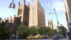 Cars and taxi cabs driving in 5th Ave traffic with churches Manhattan NYC Stock Footage