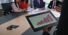 4k, An executive leading a digital presentation to colleagues in a boardroom Stock Footage