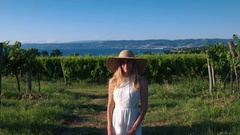 Portrait - Young woman in white dress and a sun hat standing in the vineyard Stock Footage