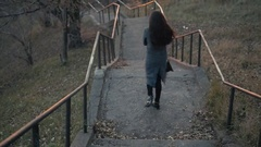 Young girl walking by the old stairs on autumm street Stock Footage