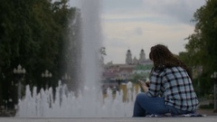 Woman relaxing near the fountain in the city listening to music, uses the phone Stock Footage
