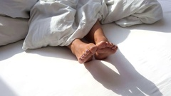 Closeup of bare feet of woman in white bed on a sunny morning Stock Footage