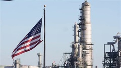 Medium shot american flag blowing in wind with power plant in background Stock Footage