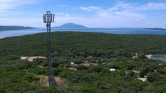 Aerial - Mobile phone base station standing just above the campsite near the sea Stock Footage