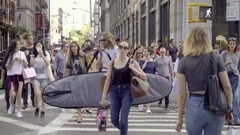 People crossing crowded street, tourists and man with surfboard summer day NYC Stock Footage